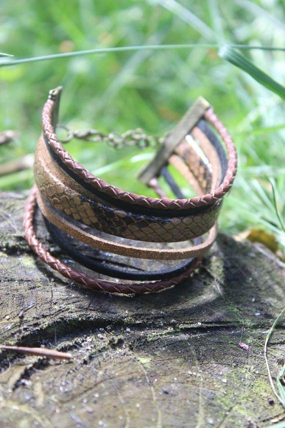 Joli bracelet fait main en cordon cuir tressé marron 3mm, cordon plat imitation serpent biface 8mm, cordon suédine noir et noisette métallisé.  On l'attache à l'aide d'un petit mousqueton avec une chainette d'extension de couleur bronze, se terminant par une breloque pistolet. Le tour de bras est de 17 à 21cm.  Page Facebook : La Roulotte à dodo