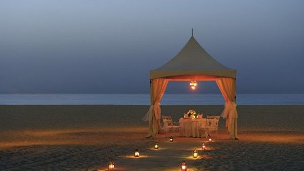Picturesque romantic location inspired candlelight sunset sea sand flowers mussels idea