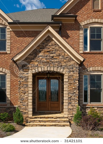 luxury model home exterior stone arch front entrance view stock photo - Luxury Homes Exterior Brick