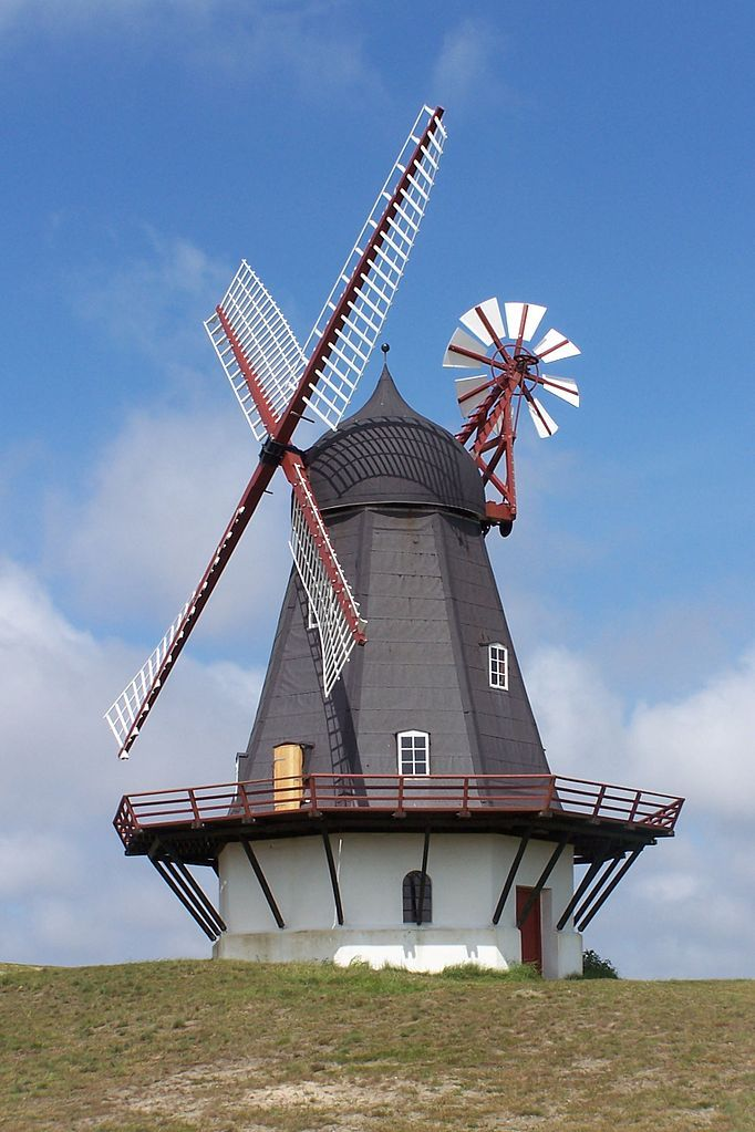 A smock mill with a stage on a brick- base in Sønderho, Fanø, Denmark --- A windmill converts the energy of wind into rotational energy by means of vanes called sails or blades. Originally windmills were developed for milling grain for food production.Then windmill was adapted to many other industrial uses. A non-milling use is to pump groundwater up with windpumps, commonly known as wind-wheels. Windmills used for generating electricity are commonly known as wind turbines.