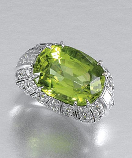 PERIDOT AND DIAMOND RING. Set to the centre with an oval peridot stated to weigh 12.44 carats, to an open work mount, millegrain-set with brilliant-cut and baguette diamonds