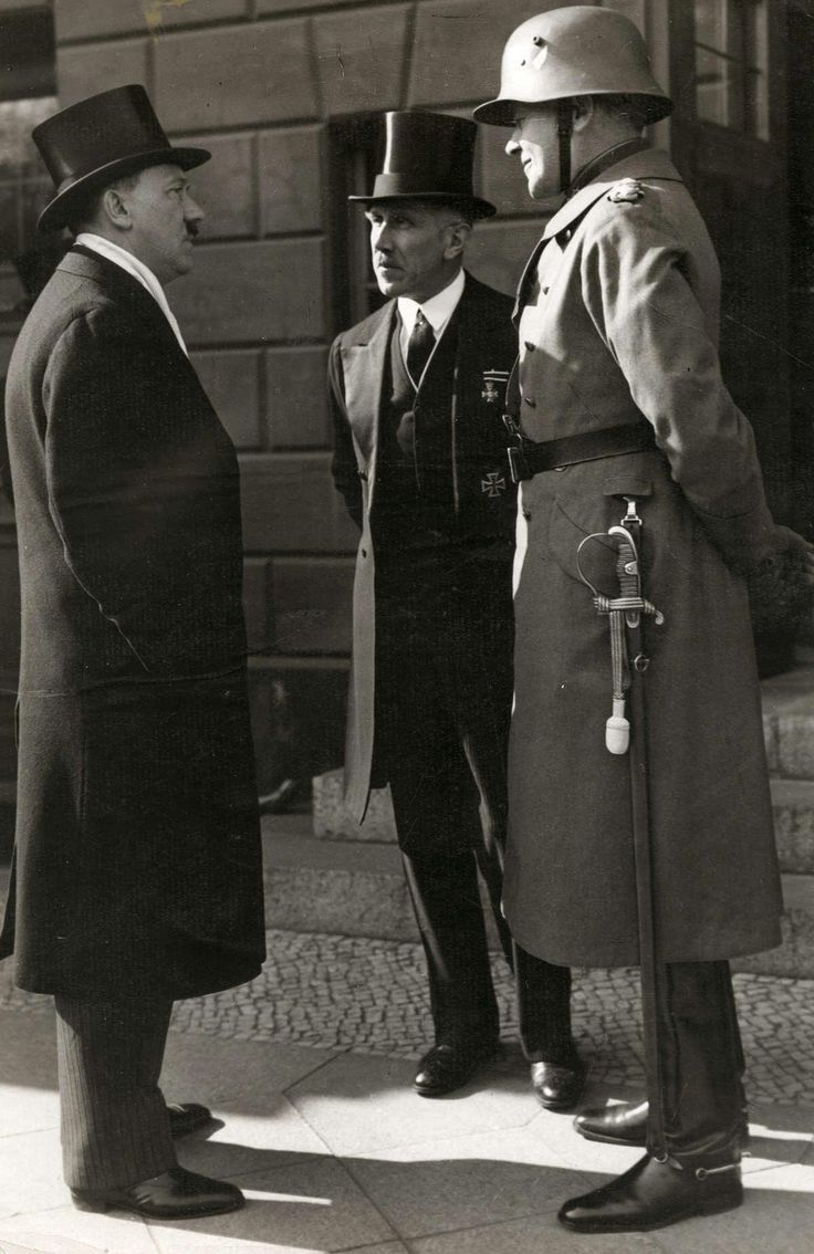 Hitler in a top hat talking to top German officials Franz von Papen and Field Marshal Werner von Blomberg outside the Berlin State Opera, Germany, 1933