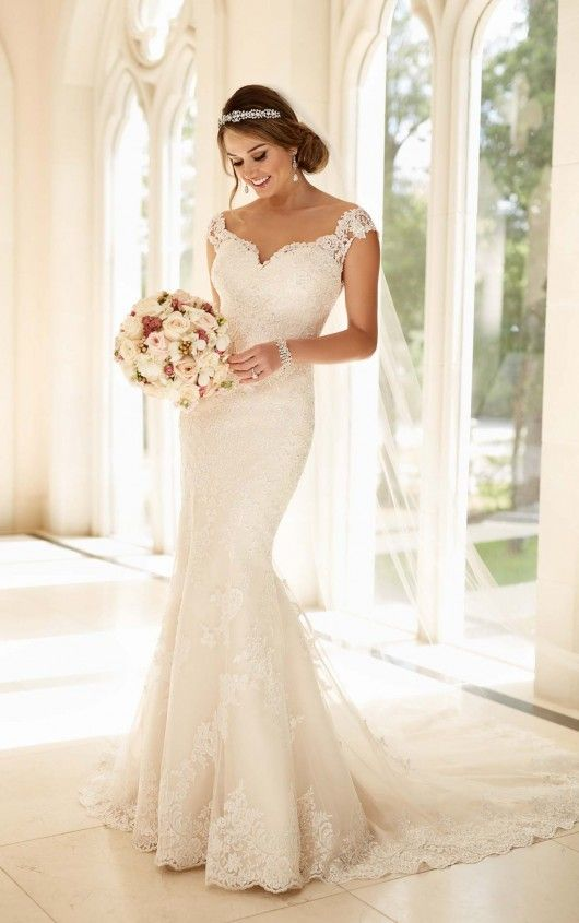 This modified fit-and-flare wedding dress from Stella York features a head-turning beaded illusion lace back that zips up with ease under lace-covered buttons. The fitted bodice has a sweetheart neckline and semi-cap sleeves that frame the face, while the skirt features hand-placed lace and the hem features pretty scalloped lace.