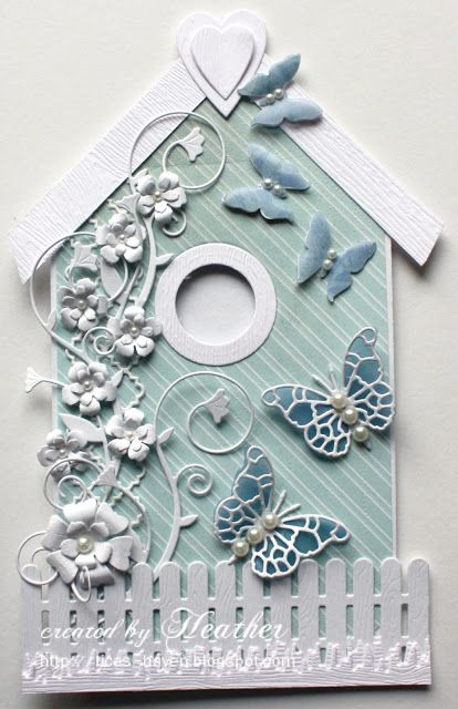 Die-namics Picket Fence & the Grass.  Memory Box Tessatina border is used as a trellis embellished with Simons Exclusive Harrington Vine, their Bella Bloom and Memory Box Fancy Blossoms.   Memory Box Pippi Butterfly and Martha Stewart Royal Butterfly