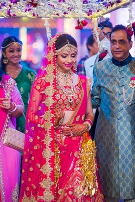 Indian Wedding Photography - Bride Entrance Ideas | WedMeGood | Bride in Hot Pink and Gold Lehenga enters under White and Purple Floral Chaadar #wedmegood #wedding #photography