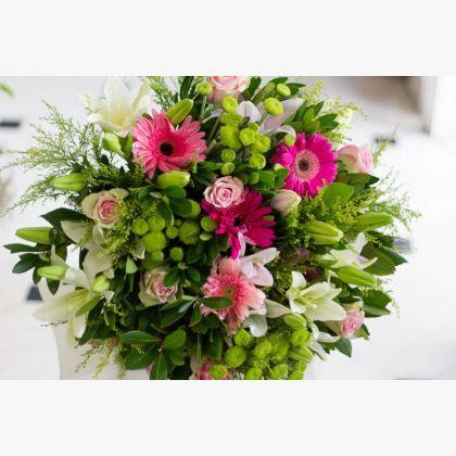 Μπουκέτο σε ροζ-φούξια αποχρώσεις με τριαντάφυλλα, λίλιουμ, ζέρμπερες, χρυσάνθεμα πομ-πομ και πρασινάδες.