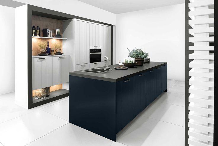 Landelijke keuken in grijs en blauw. Deze keuken springt eruit door de zowel de opstelling als de keuze van de kleuren. Er is hier bewust gekozen om twee kleuren te combineren tegen een witte achtergrond, waardoor de keuken en de kleuren enorm opvallen in de ruimte. Het kookeiland heeft donkerblauwe keukenkastjes in een matte uitvoering en een donkergrijs, mat werkblad. De keukenkasten zorgen door hun lichtgrijze kleur voor een contrast met het kookeiland. De planken aan de muur zijn ook…