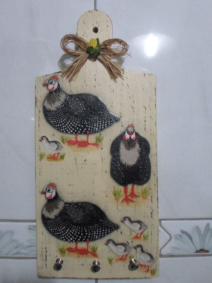 Porta chaves ou suporte para pano de prato de madeira. Peça com pintura pátina na cor bege, decoupage de tecido com motivo de galinha de angola. Possui detalhes com relevo transparente ressaltando algumas partes da decoupage, laço de palha e botão. <br>A finalização foi feita com cera. <br>Medidas: <br>Comprimento: 35cm <br>Largura: 16cm <br>Espessura lateral: 1,5cm