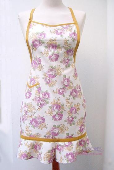Diseño exclusivo de HJ Labores. Está realizado en tela de algodón con estampado floral. Volante de capa en la falda. Bolsillo lateral.  Cintas para colocar al cuello y anudar en la cintura.
