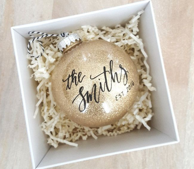 Gold Calligraphy Newlywed Christmas Ornaments. This large, sparkly gold personalized newlywed Christmas ornament is made from glittering shatterproof plastic with black and white. Add your last name and the date, which is gorgeously hand lettered in modern calligraphy style in black. It's finished with baker's twine for affixing to your tree. http://www.confettidaydreams.com/newlywed-christmas-ornaments/