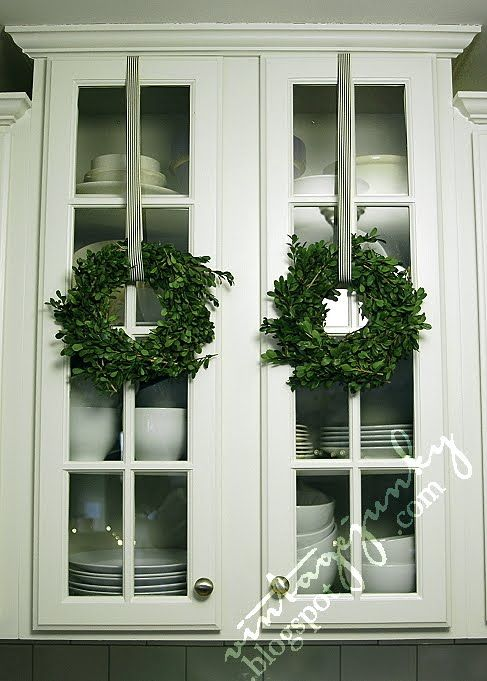 boxwood wreaths hung on cabinets: