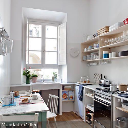 Die Küche ist in sanften Farben gehalten Stühle, Fensterläden und