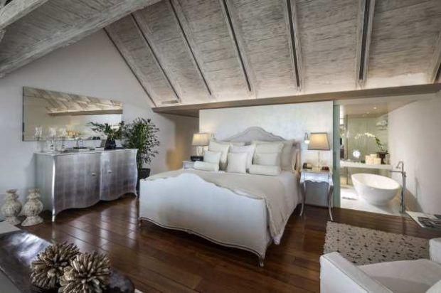 Schlafzimmer mit weißen Bett-beige-silber-Kommode-Badezimmer-freistehende-Badewanne-unter-Dach-Spiegel-Teppich-Sessel-Planzen-Lampe-Sofitel-Wohnidee