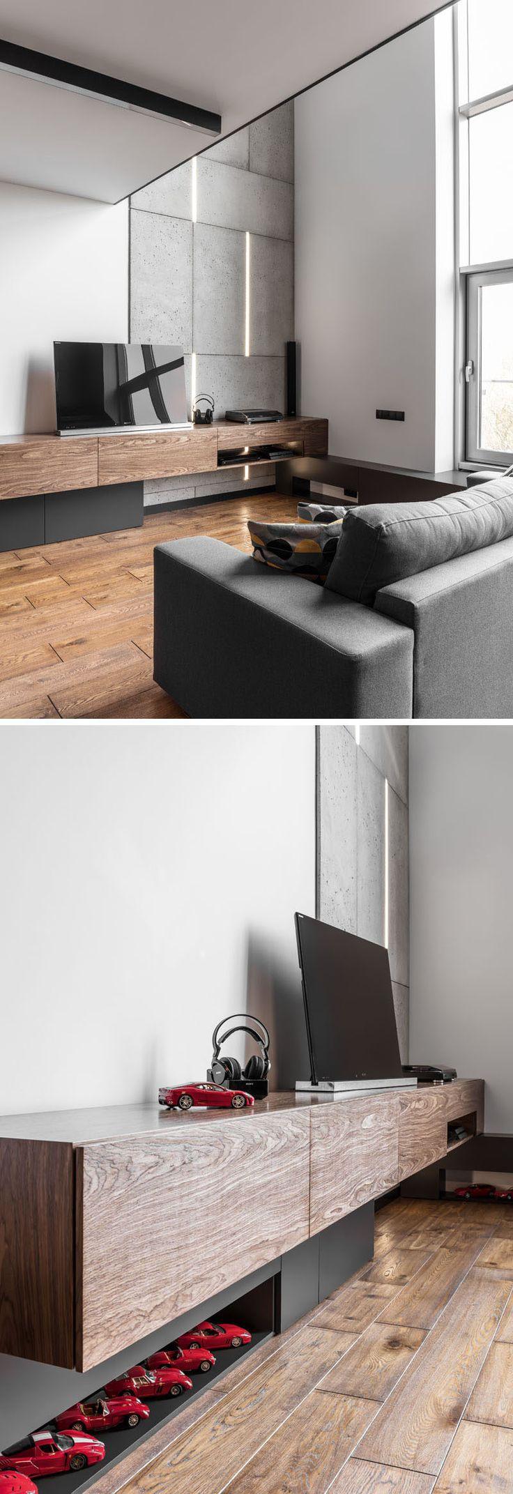 В этой простой и современной гостиной есть деревянная развлекательная консоль, в то время как стена с акцентом из бетона имеет встроенное в нее освещение, поднимая глаз вверх до высокого потолка.