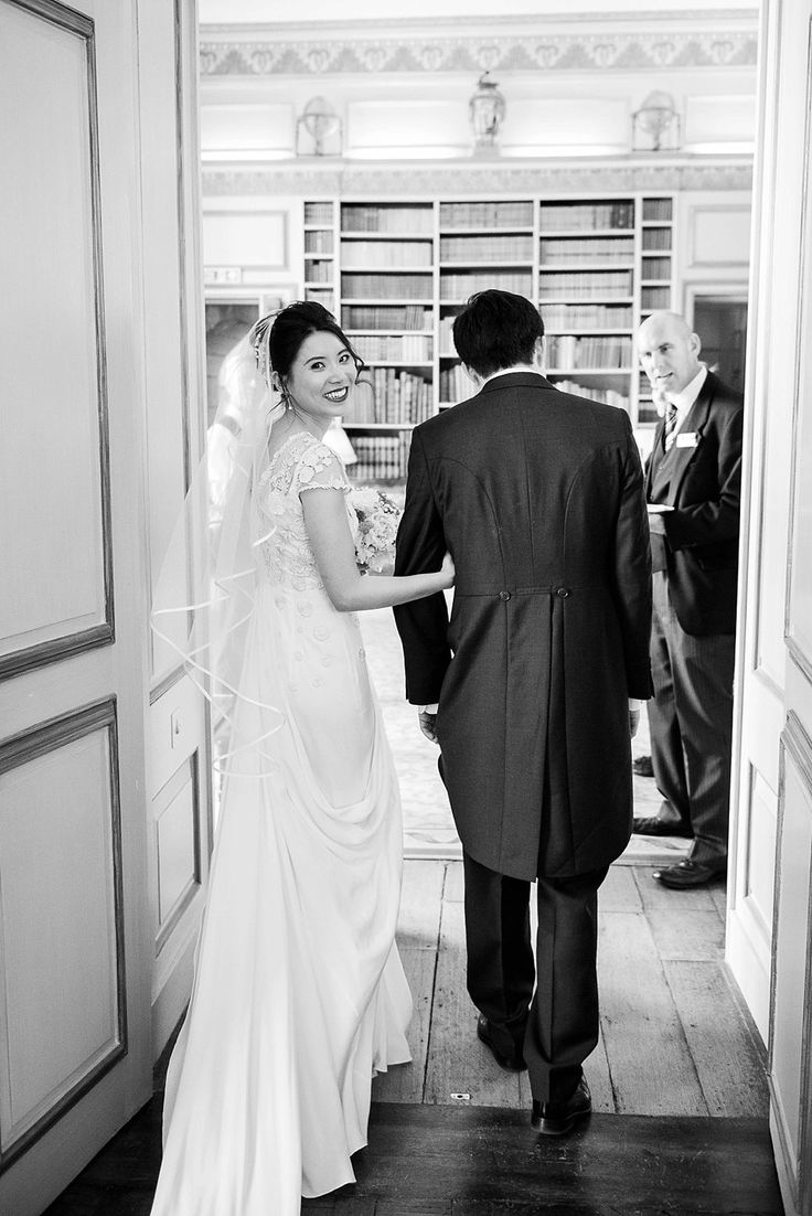 Elegant smiling bride wearing lace gown by Temperley Bridal, linking arms with groom and looking over shoulder after their marriage ceremony at Leeds Castle Kent Wedding Venue © Fiona Kelly Photography