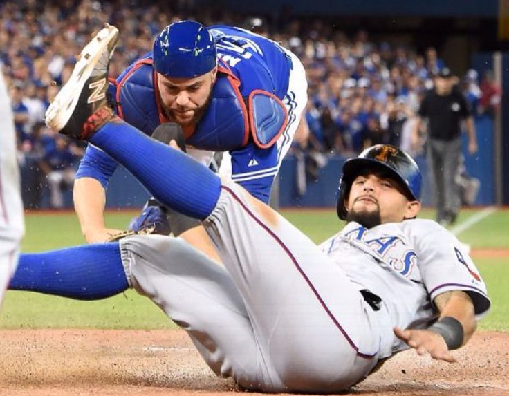 Toronto Blue Jays' catcher Russell Martin, top, tries unsuccessfully to tag out Texas Rangers' Rougned Odor who comes in to score during the 14th inning of baseball Game 2 of the American League Division Series in Toronto, Friday, Oct. 9, 2015. (Frank Gunn/The Canadian Press via AP) MANDATORY CREDIT