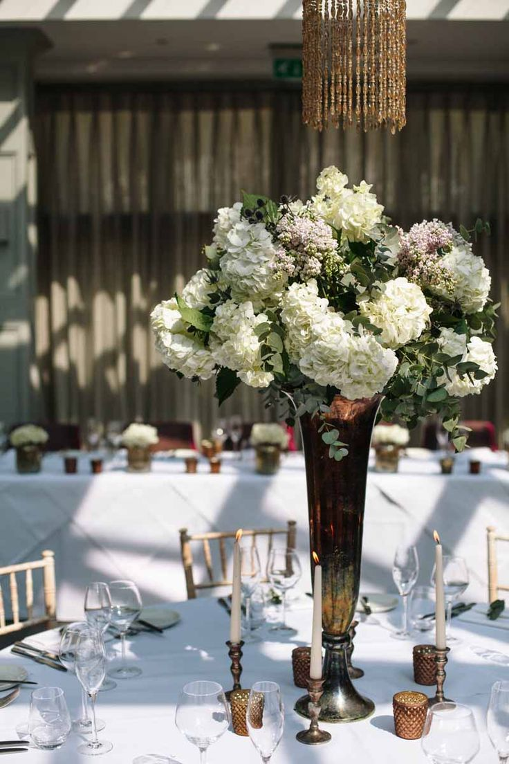 Tall wedding centrepiece bronze vases with classic white flowers at Hampton  Manor Wedding - flowers by