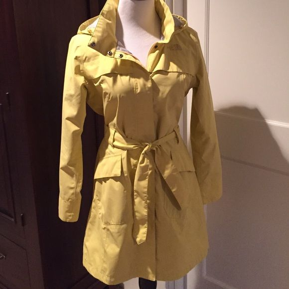 North Face Grace stunning yellow rain trench Authentic of course see pic 4. HyVent 100 polyester machine wash, dry on low or hang. Worn one season. Cuffs are perfect, no soiling. The only spots are pic 3 on the inner right arm seam. Zipper and snap front. Hood can roll into itself, but is not detachable. North Face Jackets & Coats Trench Coats