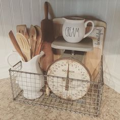 Farmhouse decor ideas: white porcelain, kitchen scale, rusty wire basket, vintage cutting boards, wooden spoons and a rolling pin