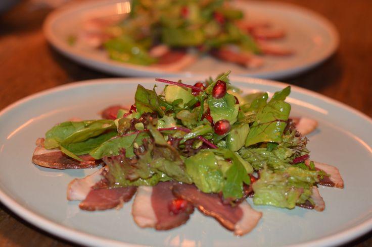 Salade met eendenborst en granaatappel. Gerookte eendenborst als voorgerecht in het kerstdiner menu. lekker met een zoetige frambozendressing