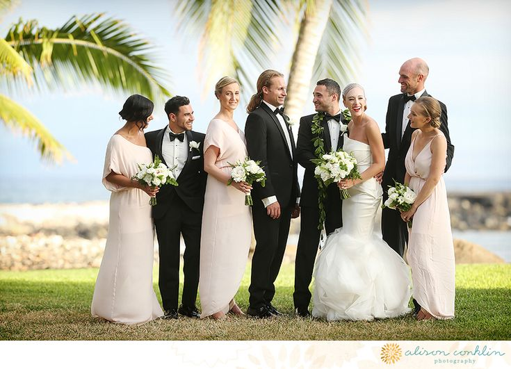 Hawaii wedding on maui bride strapless mermaid style gown with white floral bridal bouquet and groom black tuxedo with white dress shirt and black bow tie with bridal party after ceremony