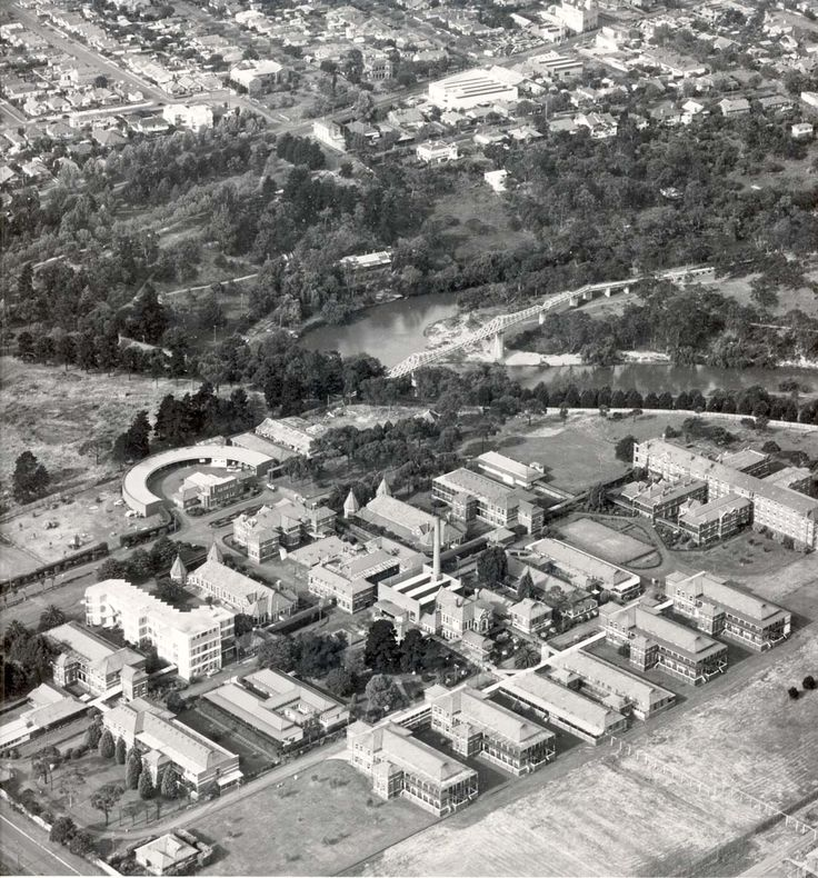 An aerial view of Fairfield Infectious Diseases Hospital. The Fairfield Park Boathouse on the Yarra River can be seen in the middle distance, with Heidelberg Road and the suburbs of Fairfield and Alphington at the top of the picture