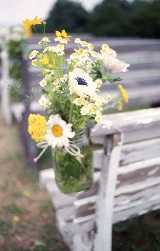 """We didn't want to spend a lot on flowers and wanted a """"just picked from a field"""" look, so that's what we did! My aunt stopped by a farm for us and bought five huge buckets of wildflowers for $75 that she and my mother-in-law made into all the bridesmaid bouquets and arrangements. I love the clean look of anemones so we ordered them wholesale for my bouquet. My sister and I made the boutonnieres out of feathers, twigs, burlap, and buttons."""