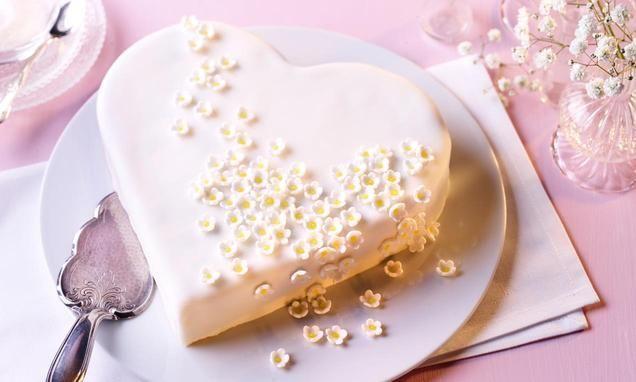 Wspaniały tort wkształcie serca zkremem waniliowym ikwiatkami zlukru plastycznego