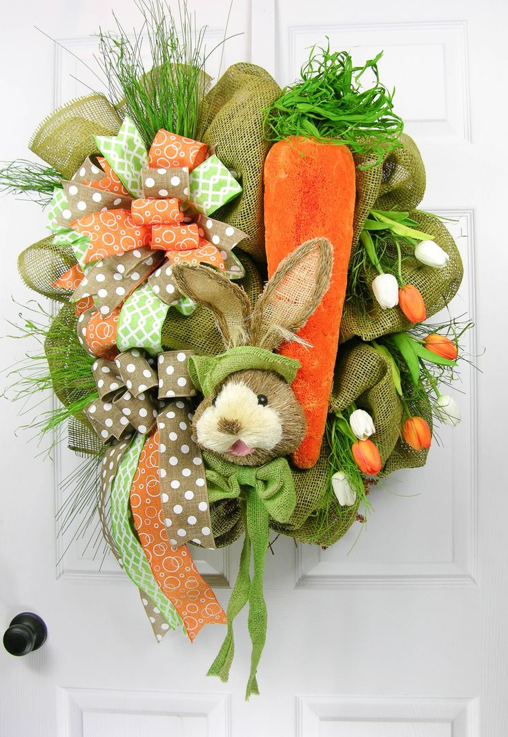 "Designer series wreath created in a one-of-a-kind design. Nestled in poofs of mossy paper mesh is a 21"" carrot with a soft green bow tied bunny. Natural grasses with soft touch tulips in white and ora"
