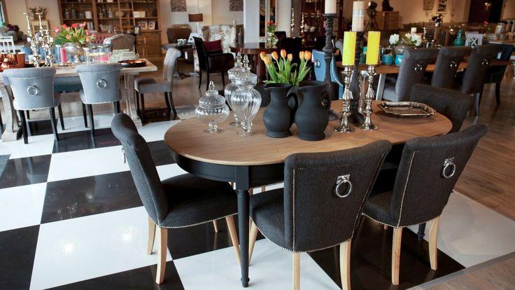 Elegancki komplet do jadalni dla 6 osób: stół o zaokrąglonych brzegach o blacie stołu w naturalnym, jasnym kolorze drewna i czarnych nogach. Krzesła tapicerowane w kolorze czarnym ze srebrnymi ćwiekami z ozdobnym uchwytem na oparciu i jasnych nogach.