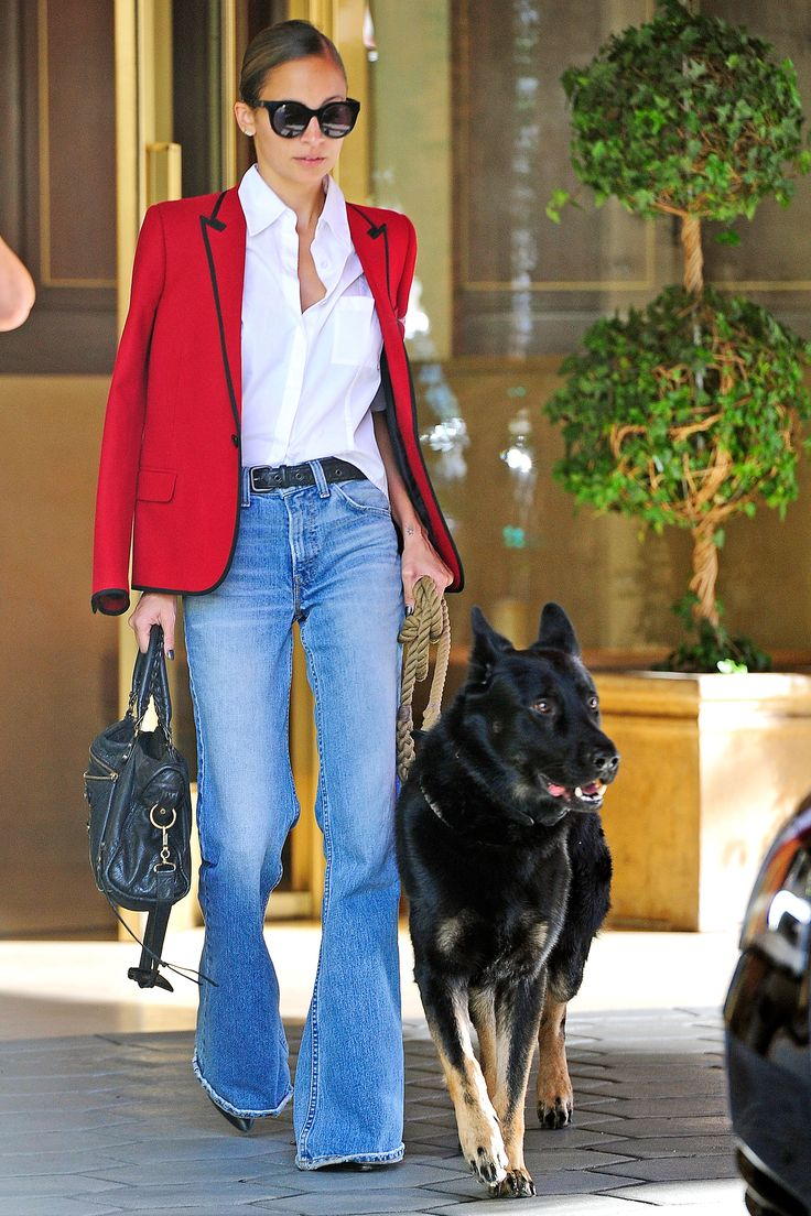 Fabulous street fashion: red blazer, white shirt, flared jeans with stiletto heels, leather bag and sunglasses to match.