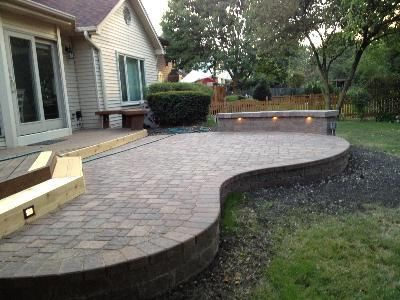 Raised paver patio with seat wall and outdoor lighting for Fireplace on raised deck