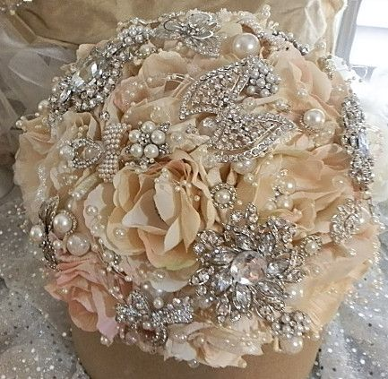 Bridal Brooch Bouquet ustom Designed Champagne Blush mix Bridal Brooch Bouquet. Bouquet is filled with elegant silver crystal brooches and pearls. Handle is in satin ivory with stunning brooch nestled in the center of the handle. http://glambouquet.com