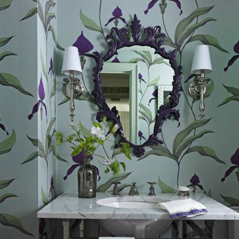 In the powder room of a whimsical prewar New York City apartment, designer Fawn Galli painted the ornate shield mirror to match the purple in Cole & Son's Orchid wall­paper.
