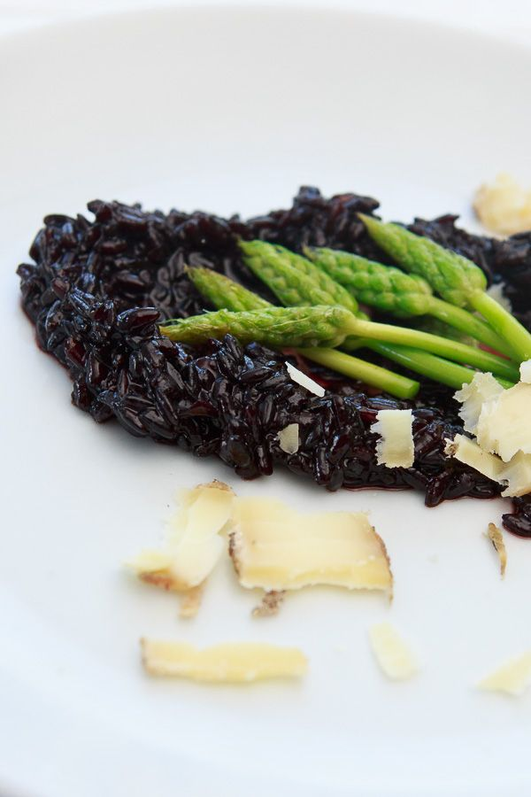 the black risotto with wild asparagus and goat cheese 200 g Riso Venere black rice 200 ml white wine 1 L chicken stock ( vegetarians take vegetable broth ) 2 shallots 2 cloves of garlic 100 g goat cheese , 1 bunch of wild asparagus , green asparagus alternatively Something rapeseed oil Salt and pepper