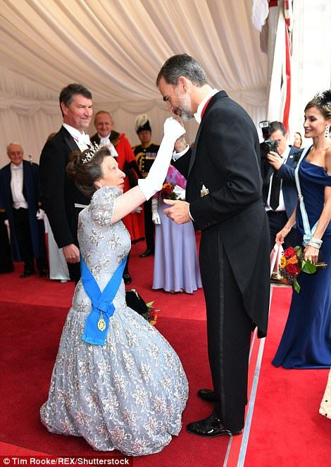 She performed a low curtsy for King Felipe, left, who looked bashful as he kissed her hand...