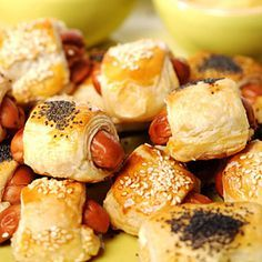 Pigs in a Blanket  1 tablespoon(s) olive oil 1 large onion, thinly sliced crosswise 2 pound(s) (about 60) mini hot dogs Cheddar cheese (optional), cut into small pieces 1 large egg All-purpose flour, for work surface 1 box(es) (17 1/2-ounce) frozen puff pastry, thawed Poppy, sesame, or mustard seeds, optional Mustard, for serving Ketchup, for serving