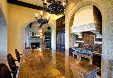 5700 Spanish oaks - mediterranean - kitchen - austin - Vanguard Studio Inc.... Love lighting, wood color... looks like knotty alder, and vent hood tucked into stonework...
