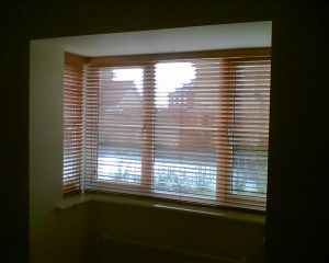 wooden venetian blinds installed in square bay window