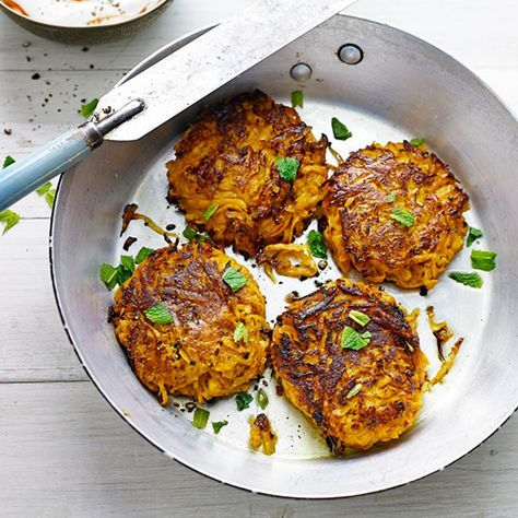 Voor de dip meng je de yoghurt en de chilisaus. Rasp de aardappels fijn en meng met de eieren, parmezaan, yoghurt, komijn, zout, peper en bloem. Vorm er 8 burgers van, bak ze in een koekenpan 4-5 minuten per...