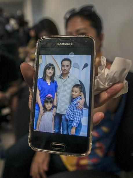 A relative shows a picture of alleged passengers who were travelling on AirAsia flight QZ8501 on her mobile phone screen at the airport in Surabaya, East Java, on December 28, 2014