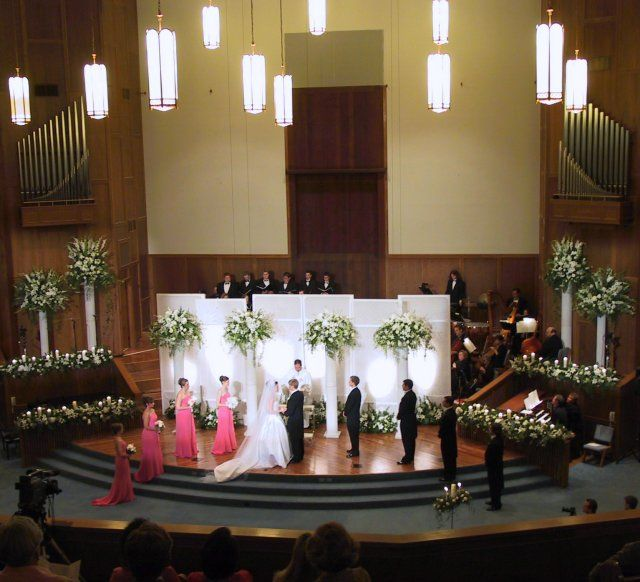 A Lovely Church Wedding. Beautiful Flowers On The Altar.