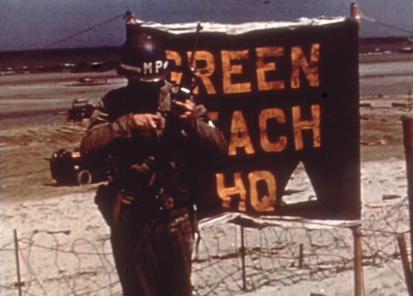 June 1944: An American military policeman checks his weapon in front of a barbed wire fence and a 'Green Beach Headquarters' sign during the Normandy Invasion, France. (Photo by Anthony Potter Collection/Getty Images)