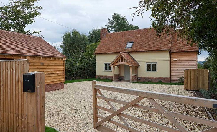 rectangular shaped self build home with central oak porch and light blue fixtures