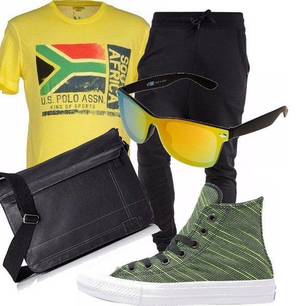 Sportivi e colorati per non perdersi nella folla. T-shirt gialla con bandiera, pantaloni neri con cavallo basso, scarpe da tennis alte e borsetta nera. Occhiali da sole polarizzati in tono con la t-shirt.