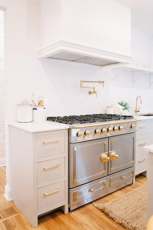 Gold and gray kitchen boasts gray cabinets adorned with brass hardware topped with white marble. A ...