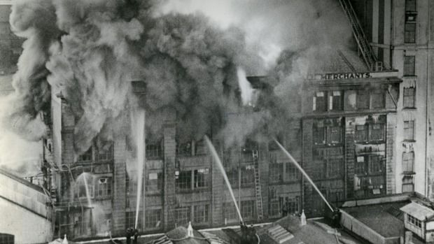Firefighters battle a towering inferno in the Hope Gibbons building in Dixon St on July 29, 1952.