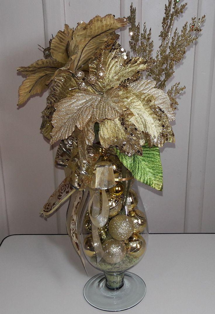 Arranjo de natal de mesa, feito com taça de vidro, bicos de papagaio, diversos tipos de bola, musgo, fitas diversas, e arranjo natalino dourado, etc.