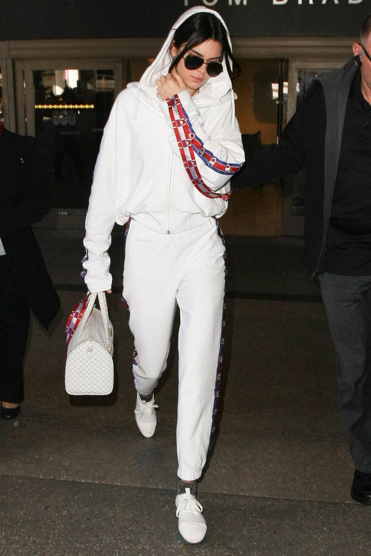 January 25, 2017 In a Vetements x Champion hoodie and sweatpants, grey knit socks, white sneakers, white duffle bag and aviator sunglasses while arriving at LAX.