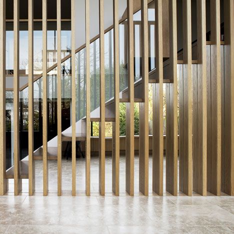 The Orangery   an oak staircase is bordered by a screen of vertical strips which mirror the steel frame of the glazing